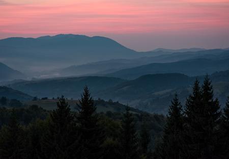 山の夜明けに赤みを帯びた空と風景の壮大な背景 写真素材