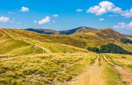 봉우리와 함께 큰 구릉 산 능선을 통해 비포장 도로. 좋은 초가을 날씨에 멋진 여행 풍경