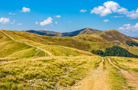 dirt road through great hilly mountain ridge with peaks. gorgeous travel scenery in fine early autumn weather Stock Photo