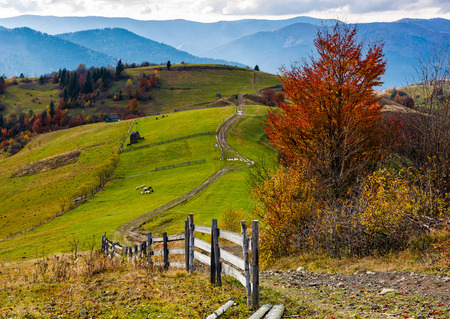 beautiful deep autumn countryside scene. wooden fence near the path through rural fields on hills in Carpathian mountainous area. Gorgeous landscape with dramatic sky over the ridge Stock Photo