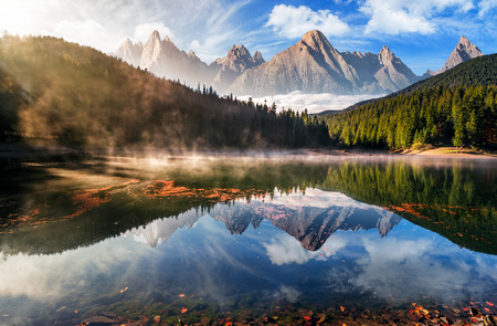 gorgeous composite mountain lake in autumn fog. lovely nature scenery with coniferous forest, rocky peaks and beautiful sky. surface of water reflects the beauty of exquisite landscape. 스톡 콘텐츠
