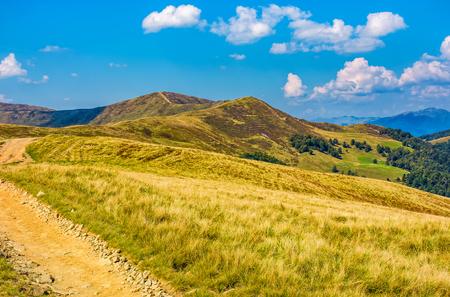 山の尾根のアルパイン丘の未舗装の道路。雲と青い空の下で天気の良い美しい初期の秋の風景