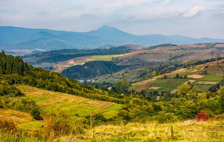 계곡에서 마을과 함께 화려한 시골. 높은 산봉우리 기슭의 아름다운 초여름 풍경