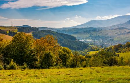 단풍 시골에서 잔디 언덕에 노란 단풍과 숲. 거리의 계곡 아래쪽에 위치한 작은 마을. 산의 아름다운 아침 풍경 스톡 콘텐츠