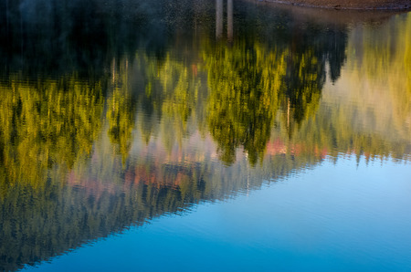 beautiful abstract nature background of lake surface reflecting spruce forest on hillside textures Stock Photo