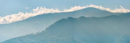 青い山の後ろに上昇し、雲のパノラマ風景。すばらしい朝背景 写真素材