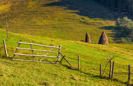 hay stacks behind the fence on rural field. lovely Carpathian countryside landscape in early autumn morning Stock Photo