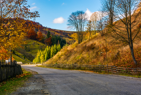fences along the road in picturesque rural area. gorgeous afternoon autumn weather in mountains Stock Photo