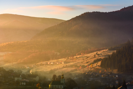 foggy sunrise in mountainous countryside. gorgeous autumnal landscape with village in mountains in fine weather