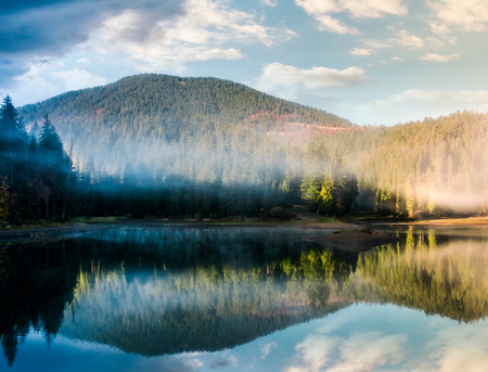 gorgeous foggy sunrise on the lake in forest. lovely autumnal landscape in mountains Stock Photo