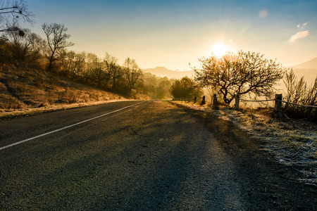 countryside road in late autumn fog at sunrise. dangerous transportation area in mountains Stock Photo
