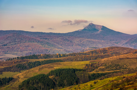 high mountain peak behind the hills with forest and meadows. gorgeous countryside landscape Stock Photo - 85948474