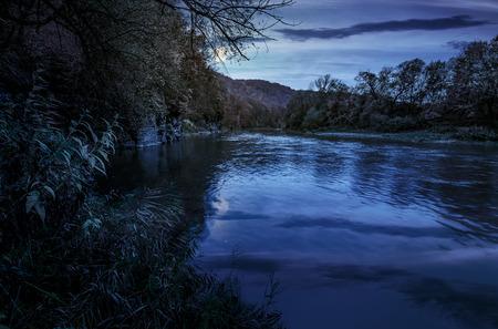 秋の山の森林川。黄ばんだ木と岩の崖の素敵な草で覆われた海岸。満月の光で夜、豪華な自然秋色