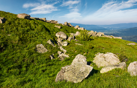 huge boulders on a grassy slope in mountains. lovely mountain landscape with sky full of beautiful clouds Stock Photo