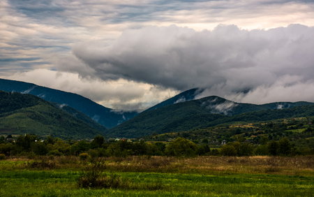clouds rise in mountains on overcast morning. lovely countryside scenery with village at the foot on the mountain in autumn weather Stock Photo - 86261761
