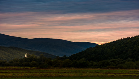 church dome over the forest in valley at dawn. mysterious countryside autumn landscape Stock Photo
