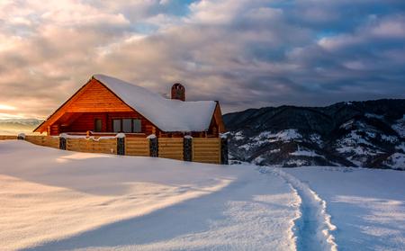 日の出で深い雪の中で木造シャレーへのパス。冬の山、素晴らしい場所の休暇のための豪華な風景 写真素材