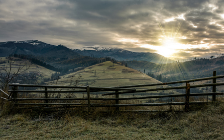 fence on hillside in late autumn gloomy sunrise. high mountain ridge with snowy tops in a distance under overcast sky Stock Photo
