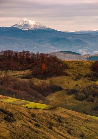 Verschneiter Gipfel hinter den sanften Hügeln im Herbst unter bewölktem Himmel Standard-Bild - 86516077