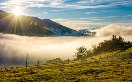 rural valley at foggy sunrise in autumn. wooden fence on the hillside with woodshed and orchard. gorgeous autumnal landscape with high mountains in a distance.