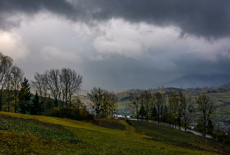 rural fields on serpentine in bad weather. mountainous countryside with trees in autumn stormy evening Stock Photo