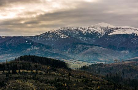Bergrücken mit schneebedecktem Gipfel an trüben Tag. geheimnisvolle Spätherbstlandschaft bei schlechtem Wetter mit bedecktem Himmel Standard-Bild - 86584959