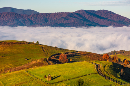gorgeous morning in mountainous rural area in autumn. wooden fence along the grassy rolling hills with hay stacks fall in to the valley with thick rising fog Stock Photo