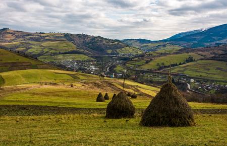 Heuhaufen auf Wiese im Herbst Berge. Dorf und Eisenbahn sind im Tal zu sehen Standard-Bild - 86944601