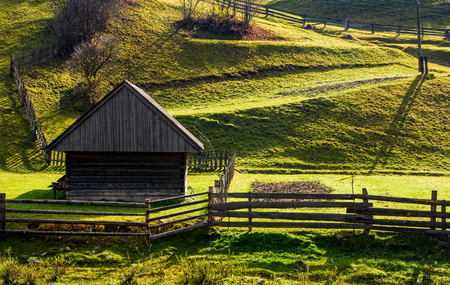 enclose: woodshed near the fence on grassy hillside. beautiful rural scenery in autumn
