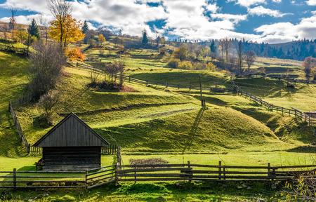 schuur in de buurt van het hek op met gras begroeide heuvels. mooi landelijk landschap in de herfst met bewolkte ochtendhemel