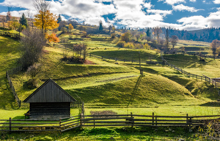 woodshed near the fence on grassy hillside. beautiful rural scenery in autumn with cloudy morning sky