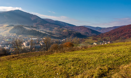 grassy hillside over the village in valley. beautiful mountainous rural area scenery in autumn Stock fotó