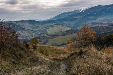 dirt road through mountainous countryside. beautiful late autumn scenery with snowy tops of high mountain ridge in a distance