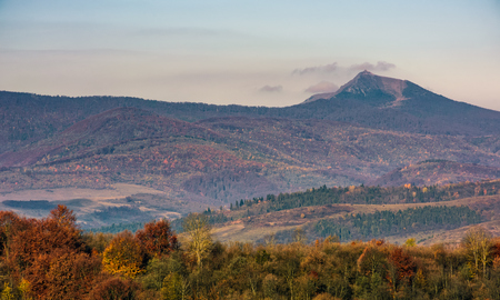 ridge with high peak above hills with forest. lovely mountainous background in late autumn Stock Photo
