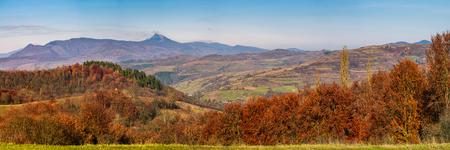 山で豪華な秋の田舎パノラマ。なだらかな丘、距離の高峰と谷と山のリッジの村に紅葉と森。カルパティア山脈の美しい風景