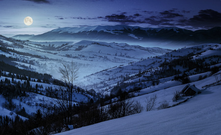beautiful countryside in mountains at night. village and rural fields on hillsides of valley covered with snow shine in full moon light