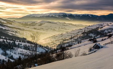 日の出山の美しい田園地帯。朝の光で雪の輝きで覆われて村と田舎の田畑で渓谷の斜面 写真素材
