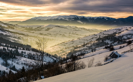 beautiful countryside in mountains at sunrise. village and rural fields on hillsides of valley covered with snow shine in morning light Stock Photo