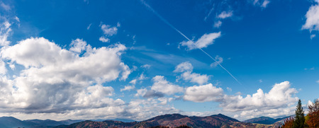 beautiful cloudscape over the mountain ridge. lovely nature background with blue sky and fluffy clouds on autumn day Stock Photo