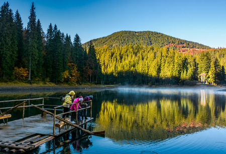 National Park Synevyr, Ukraine - October 23, 2016: tourists on Synevyr lake feed fish from the raft. high altitude mountain lake among spruce forest on beautiful foggy morning Stock Photo - 87034112
