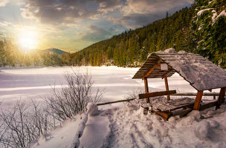 wooden bower in snowy winter spruce forest. beautiful mountainous landscape near snow covered frozen lake at sunset 版權商用圖片