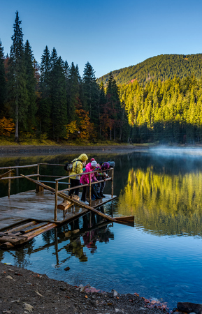National Park Synevyr, Ukraine - October 23, 2016: tourists on Synevyr lake feed fish from the raft. high altitude mountain lake among spruce forest on beautiful foggy morning Stock Photo - 87034114