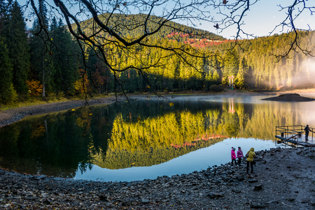 National Park Synevyr, Ukraine - October 23, 2016: tourists on Synevyr lake in autumn. high altitude mountain lake among spruce forest. The most visited place in Carpathians on beautiful foggy morning Editorial