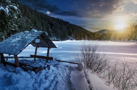 낮과 밤 시간 변경 개념 나무 박 혀와 가문비 나무 숲에서 겨울. 눈 근처의 아름 다운 산악 풍경 태양과 달와 얼어 붙은 호수 덮여 스톡 콘텐츠