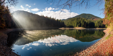 gorgeous foggy morning on the mountain lake. beautiful moment of sun rays path through forest and fog. lovely panoramic autumn scenery Stock Photo