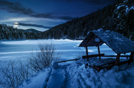 wooden bower in snowy winter spruce forest. beautiful mountainous landscape near snow covered frozen lake at night in full moon light Stock Photo