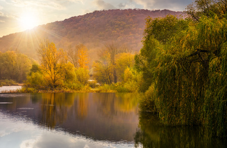 landscape with calm river in autumn at sunset. beautiful mountainous scenery with red and yellow foliage