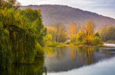 Landschaft mit ruhigem Fluss im Herbst. schöne bergige Landschaft mit roten und gelben Blättern Standard-Bild - 87639082