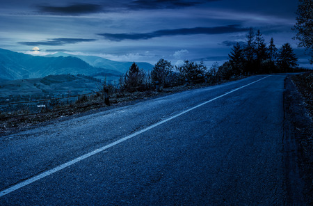 countryside road through mountains at night in full moon light. lovely autumnal scenery Stock Photo