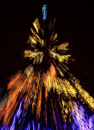 Abstracte Kerstmis steekt achtergrond aan bij nacht. Kerstboom wazig met zoom-effect Stockfoto